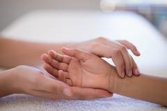Primo piano del polso d'esame del terapista femminile sull'asciugamano bianco fotografie stock libere da diritti