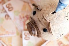 Primo piano del porcellino salvadanaio e delle banconote turche Immagini Stock