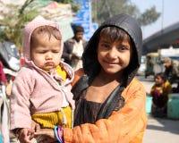 Primo piano del ragazzo povero con un bambino Nuova Delhi India Fotografia Stock