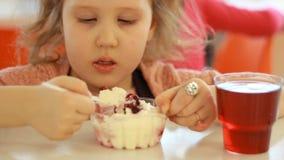 Primo piano del ritratto di un bambino che mangia dessert e che beve succo nel caffè Il bambino mangia il gelato stock footage