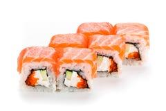Primo piano del rotolo di sushi Sushi con il salmone, il caviale e Philadelphia isolati su fondo bianco Immagine Stock