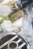 Primo piano del rubinetto del ferro chiuso, con una goccia di acqua Fotografia Stock