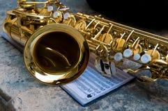 Primo piano del sassofono insieme alle note Immagini Stock Libere da Diritti