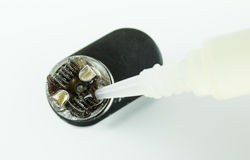 Primo piano del succo della sgocciolatura sulle bobine di una e-sigaretta immagine stock