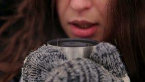 Primo piano del tè bevente della ragazza nell'inverno sulla via archivi video