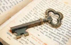 Primo piano del tasto disposto sulla bibbia dell'annata Fotografia Stock