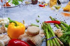 Primo piano del tavolo da cucina con le verdure crude variopinte ed il condimento Vari ingredienti su un fondo di pietra Immagini Stock