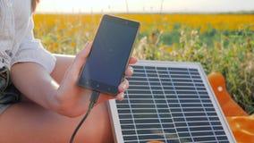 Primo piano del telefono cellulare, all'aperto alimentato solare del caricabatteria, energia rinnovabile, fine sul telefono cellu stock footage