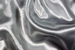 Primo piano del tessuto d'argento molle coperto del raso Fotografie Stock