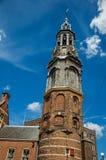 Primo piano del tetto aguzzo del campanile in una costruzione di mattone con l'orologio ed il cielo blu dorati a Amsterdam Immagini Stock Libere da Diritti