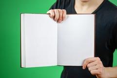 Primo piano del tipo in maglietta nera che tiene il libro bianco aperto dello spazio in bianco sopra Fotografia Stock