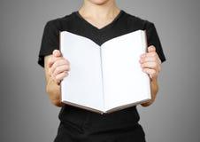 Primo piano del tipo in maglietta nera che tiene il libro bianco aperto dello spazio in bianco sopra Immagine Stock