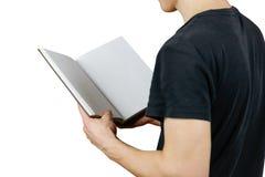 Primo piano del tipo in maglietta nera che tiene il libro bianco aperto dello spazio in bianco sopra Fotografie Stock Libere da Diritti