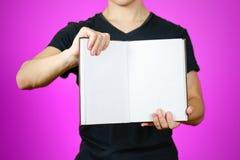 Primo piano del tipo in maglietta nera che tiene il libro bianco aperto dello spazio in bianco sopra Immagini Stock