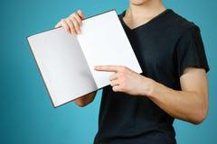 Primo piano del tipo in maglietta nera che tiene il libro bianco aperto dello spazio in bianco sopra Fotografie Stock