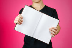 Primo piano del tipo in maglietta nera che tiene il libro bianco aperto dello spazio in bianco sopra Fotografia Stock Libera da Diritti