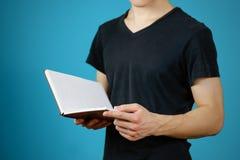 Primo piano del tipo in maglietta nera che tiene il libro bianco aperto dello spazio in bianco sopra Immagini Stock Libere da Diritti