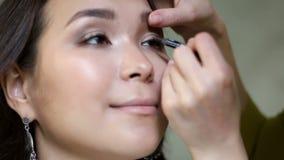 Primo piano del truccatore professionista che applica eye-liner sulla palpebra archivi video