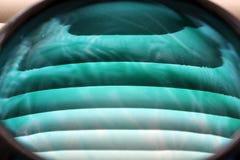 Primo piano del vaso di vetro blu contro i ciechi fotografia stock