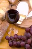 Primo piano del vetro di vino con alimento nella priorità bassa Fotografie Stock