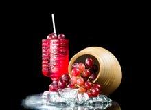 Primo piano del vino rosso di vetro dell'uva un fondo nero Fotografia Stock Libera da Diritti