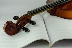 Primo piano del violino e dello strato in bianco della nota Fotografia Stock Libera da Diritti