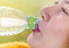 Primo piano dell'acqua potabile della giovane donna all'allenamento all'aperto Fotografie Stock Libere da Diritti