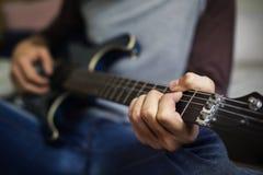 Primo piano dell'adolescente che gioca chitarra immagine stock