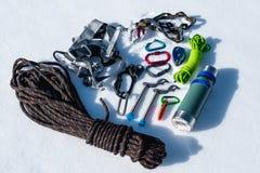 Primo piano dell'attrezzatura rampicante di inverno su neve fresca un giorno soleggiato Carabine con un gazebo della corda e zhum Fotografia Stock