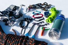 Primo piano dell'attrezzatura rampicante di inverno su neve fresca un giorno soleggiato Carabine con un gazebo della corda e zhum Fotografie Stock