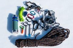 Primo piano dell'attrezzatura rampicante di inverno su neve fresca un giorno soleggiato Carabine con un gazebo della corda e zhum Immagini Stock Libere da Diritti
