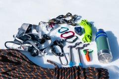 Primo piano dell'attrezzatura rampicante di inverno su neve fresca un giorno soleggiato Carabine con un gazebo della corda e zhum Immagine Stock
