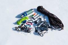 Primo piano dell'attrezzatura rampicante di inverno su neve fresca un giorno soleggiato Carabine con un gazebo della corda e zhum Immagini Stock