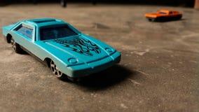 Primo piano dell'automobile blu del giocattolo per i bambini su diverso fondo con l'automobile arancio del giocattolo su fondo fotografia stock