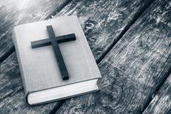 Primo piano dell'incrocio cristiano di legno sulla bibbia sulla vecchia tavola fotografie stock