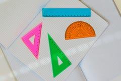 Primo piano dell'insieme degli strumenti colorati per la geometria su fondo di grandi taccuini vuoti aperti in una gabbia, vista  Fotografie Stock Libere da Diritti