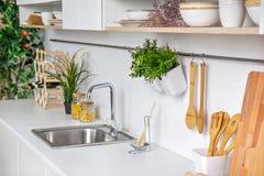 Primo piano dell'interno della cucina bianca moderna con articolo da cucina ed il mandarino di legno su fondo Fotografia Stock