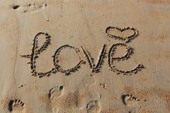 """Primo piano dell'iscrizione """"di amore """", di un simbolo di cuore e delle orme nella sabbia fotografie stock libere da diritti"""