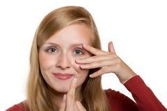 Primo piano dell'occhio blu della donna con l'applicazione della lente a contatto Immagini Stock