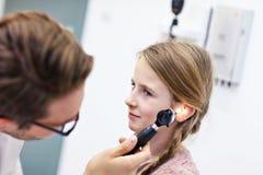 Primo piano dell'orecchio del dottore Examining Girl maschio con un otoscopio immagine stock libera da diritti