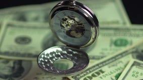 Primo piano dell'orologio da tasca d'annata che appende sopra i soldi, tempo prezioso che passa vicino archivi video
