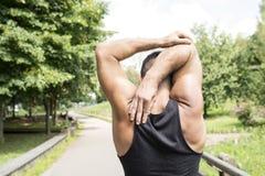 Primo piano dell'uomo atletico posteriore che fa gli allungamenti prima dell'esercitazione, Immagini Stock