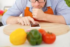 Primo piano dell'uomo che indica dito lo smartphone n i precedenti della cucina Fotografia Stock