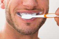 Primo piano dell'uomo che pulisce i suoi denti fotografia stock libera da diritti