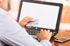 Primo piano dell'uomo che si siede dallo scrittorio con il computer portatile Immagine Stock Libera da Diritti