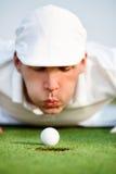 Primo piano dell'uomo che soffia sulla palla da golf Fotografie Stock