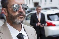 Primo piano dell'uomo con gli occhiali da sole e dell'uomo d'affari nei precedenti Fotografia Stock Libera da Diritti
