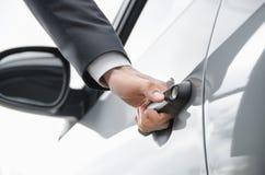 Primo piano dell'uomo d'affari che apre una porta di automobile Fotografia Stock