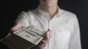 Primo piano dell'uomo d'affari che dà un barilotto delle banconote in dollari Il concetto degli stipendi carità archivi video