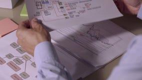 Primo piano dell'uomo d'affari che guarda attraverso i documenti dal suo caso del documento Controlla sui diagrammi e sugli schem video d archivio
